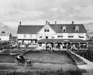 1906 photo Hotel Sierra, Loyalton, California, with people standing on porch, people in automobile in foreground, and mountains in background graphic.